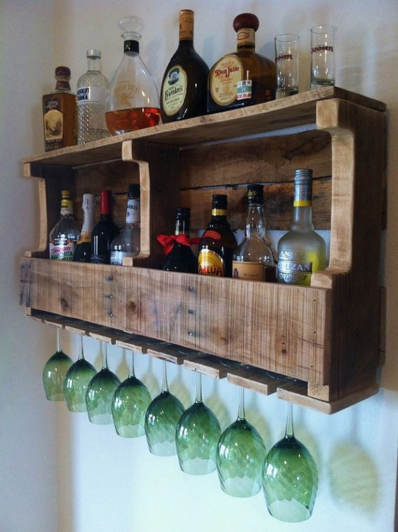 a rustic pallet wine rack with wine bottles and liquors and storage for glasses
