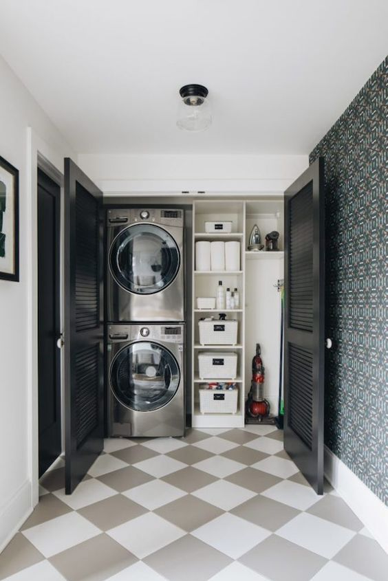 a small laundry built into an awkward nook of your home and hidden with black shutter doors