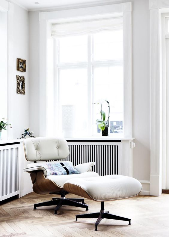 a white leather and plywood chair with comfy armrests and a matching footrest have ultimate design and are veyr comfy