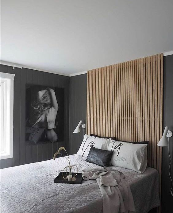 a contemporary monochromatic bedroom with a sleek woodne plank headboard that goes up the wall to the ceiling