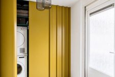 25 a small laundry placed right in an entryway and hidden behind mustard-colored sliding doors