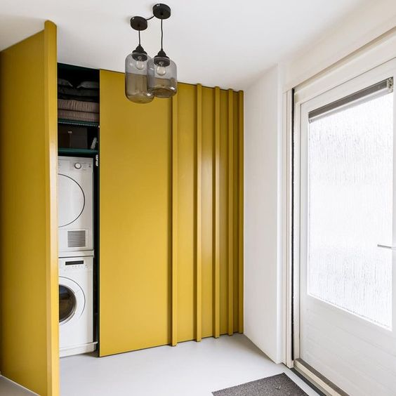 a small laundry placed right in an entryway and hidden behind mustard-colored sliding doors
