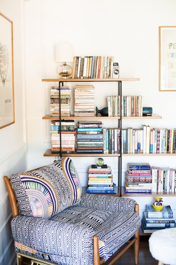 a wooden chair with bright printed upholstery and a large open shelf will make your reading nook boho-like