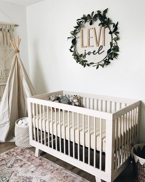 the name placed on the wall and accented with a fake greenery wreath is a stylish idea for a gender-neutral nursery