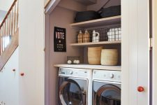 26 a stylish and functional laundry hidden under the stairs behind simple white doors