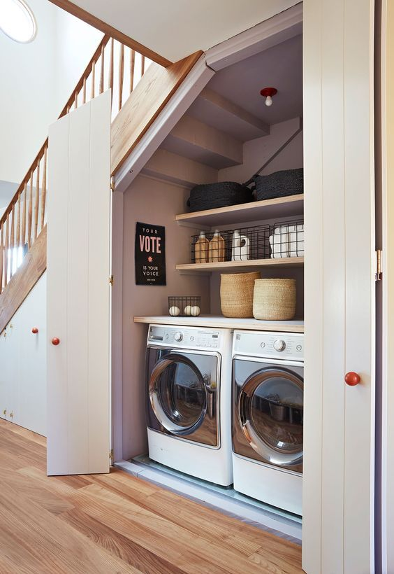 a stylish and functional laundry hidden under the stairs behind simple white doors