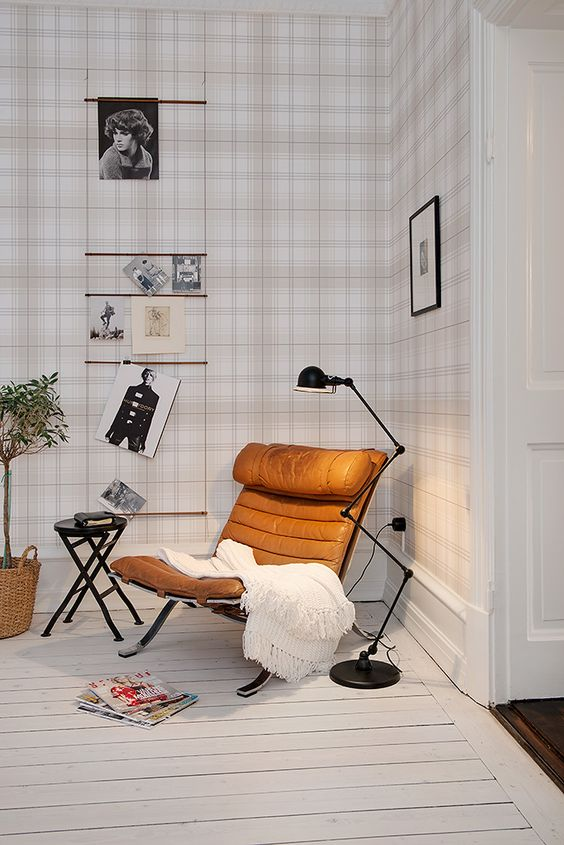 an amber leather chair, a floor lamp and a blanket for comfortable reading and enjoying coziness