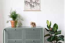 a Nikkeby sideboard by IKEA done in olive and with cane webbing is a stylish way to add a bit of color and chic to the space