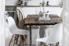 a Scandinavian kitchen in white, with stone countertops, a metal pendant lamp, a rough wooden table, white chairs