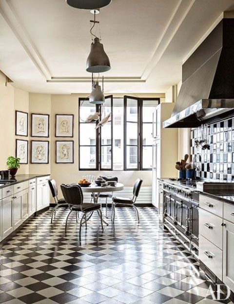a bold kitchen in black and white, with a tiled floor, a tiled backsplash, blakc chairs and a round table, metal pendant lamps
