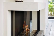a built-in fireplace with a glass cover and a stone base is a beautiful and cool idea for a contemporary space