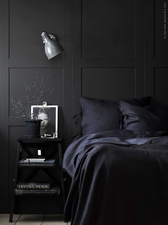 a chic Nordic moody bedroom with black paneling, navy bedding and black furniture plus a sconce