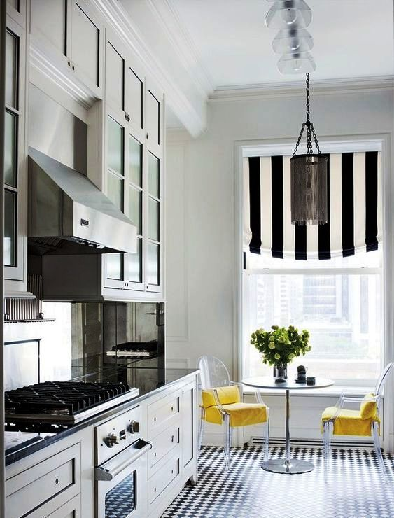 a chic kitchen with farmhouse cabinetry, a striped curtain that echoes with the floors, a round table and acrylic chairs with yellow upholstery