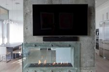a contemporary built-in fireplace built into a raw concrete wall, with a glass cover looks rough and very catchy