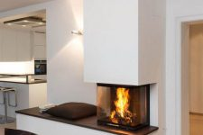 a contemporary fireplace with a bench to enjoy it and a glass cover to make the fire all-visible