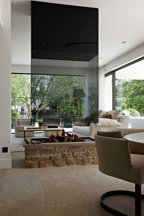 a contemporary fireplace with a brick base, a metal frame and a dark glass hood is a very cozy decoration for your space