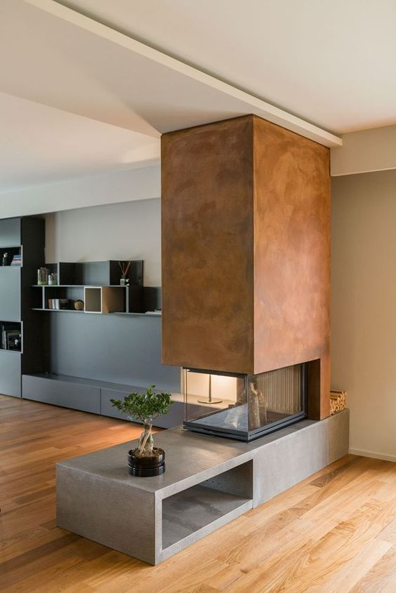 a contemporary fireplace with a concrete base, a metal hood and a glass cover looks contrasting and very bold