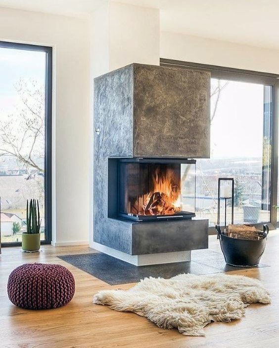 a contemporary fireplace with a glass cover, some firewood in a leather basket and soem faux fur