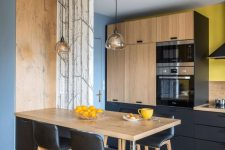 a contemporary kitchen in black and light-colored wood, with pendant lamps, black leather stools and bright yellow touches