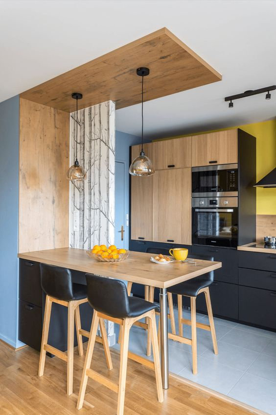a contemporary kitchen in black and light colored wood, with pendant lamps, black leather stools and bright yellow touches