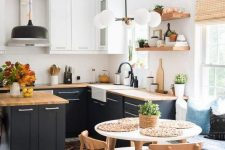 a contemporary kitchen with black and white cabinets, wooden countertops, mid-century modern lamps and a dining zone with a round table and chairs