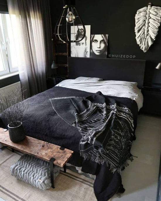 a contemporary moody bedroom with black walls, black furniture and a wooden bench, pendant lamps and art