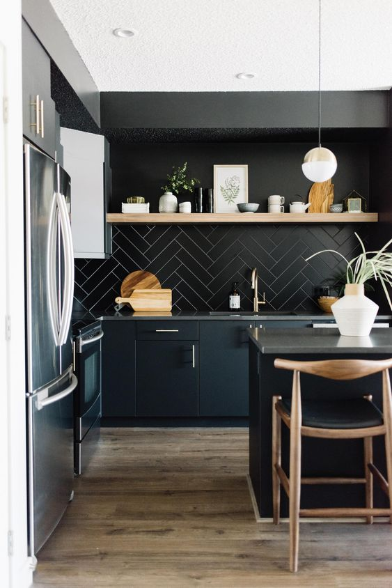 a contemporary moody kitchen with sleek black cabinetry, a black tile backsplash, a wooden shelf and wooden stools and pendant lamps