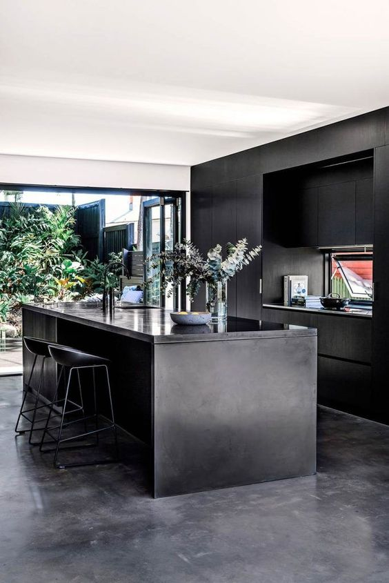 a contemporary moody kitchen with sleek black cabinetry, a kitchen island, a glazed wall with an entrance to a courtyard