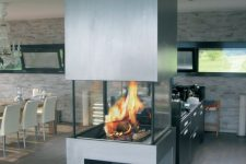 a contemporary steel clad fireplace with a glass cover and a firewood storage space is a stylish addiiton to the kitchen