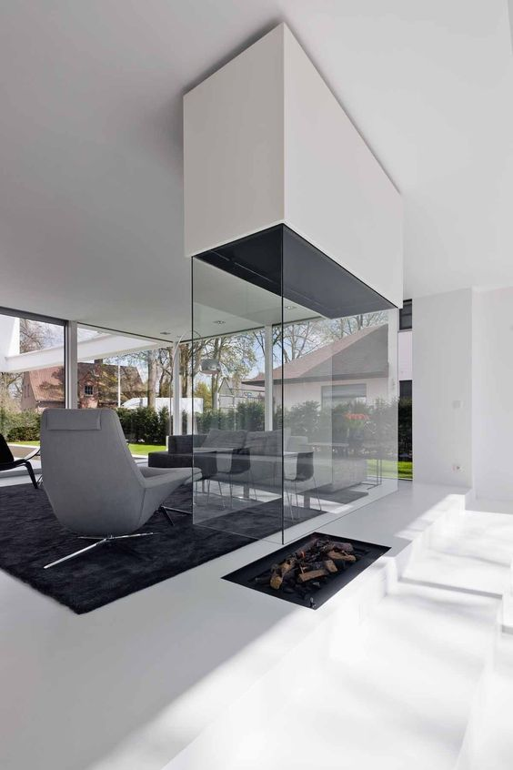 a contemproary fireplace built into the floor, with a white hood and a glass cover is a stylish idea to go for