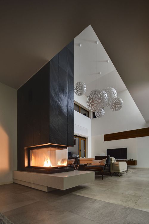 a contrasting contemporary fireplace in black and white, with a glass cover is a gorgeous space divider and cozying up piece