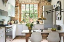 a cottage kitchen with white cabinetry, stone countertops, a brick wall, metal appliances and a vintage wooden table and white chairs
