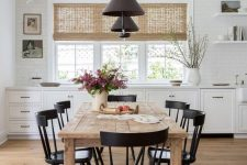 a cozy farmhouse kitchen with white lower cabinets, a rough wood dining table, black chairs and black pendant lamps