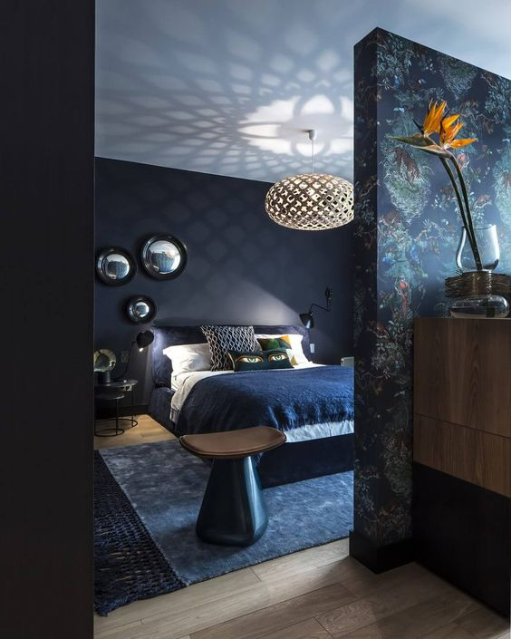 a dark and moody bedroom with navy walls and a white ceiling, black modern furniture, a printed statement wall and an arrangement of mirrors