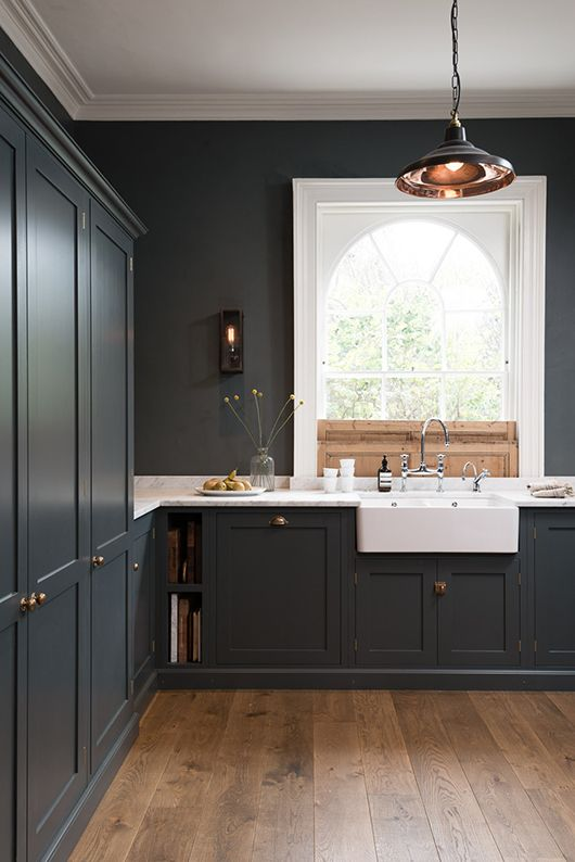 a dark and moody kitchen with graphite grey cabinetry, white marble countertops, a pendant lamp is very elegant and simple