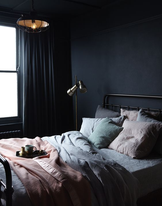 a dark minimalist bedroom with a metal bed, a floor and a pendant lamp, pastel bedding and dak curtains