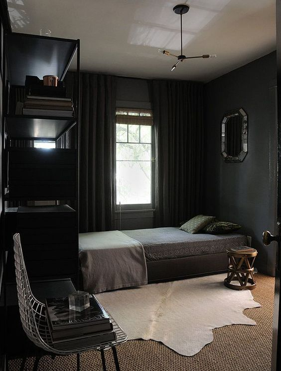 a dark vintage bedroom with black walls, black furniture and curtains, a wooden stool and a mirror on the wall