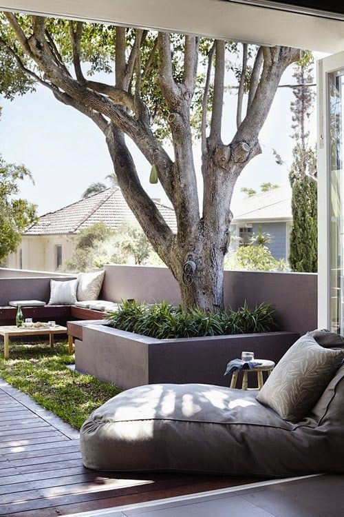 a deck with a built in wooden bench, with some greenery and a tree and a soft lounger is a welcoming space to be