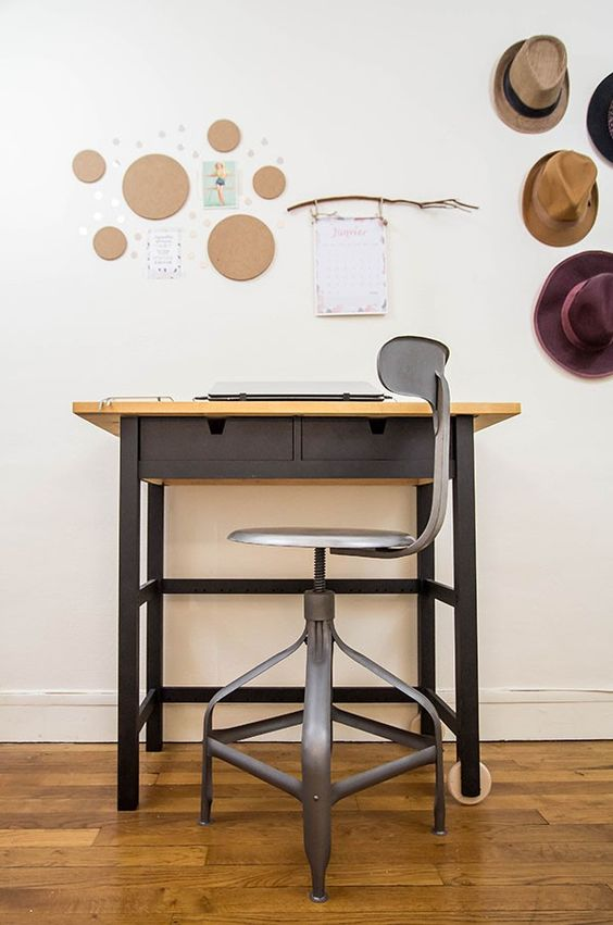 a desk with a black IKEA Forhoja cart with a neutral wooden countertop and a matching black stool