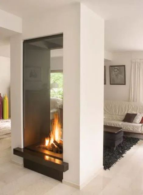 a double-sided tall fireplace clad in glass is a bold contrasting idea that can serve a space divider