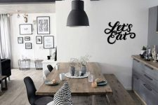 a graphite grey farmhouse kitchen with wooden countertops, a wooden table and a bench, black chairs and pendant lamps