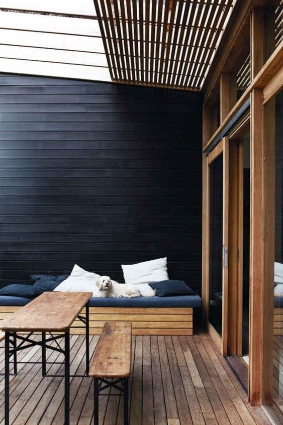 a minimal deck with a black wlal, a wooden bench and a wooden dining set plus black and white textiles