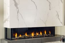 a minimalist fireplace with a dark tile base and a white marble hood plus a glass cover is a very refined idea