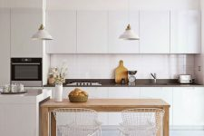 a minimalist kitchen in white, with a black countertop, a small wooden table for a contrast and a soft touch and metal chairs