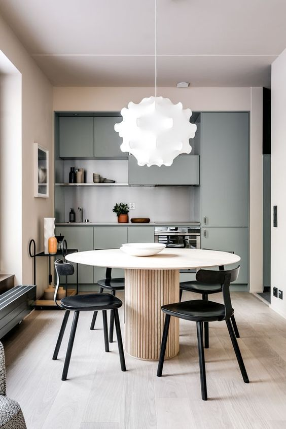 a minimalist kitchen with green cabinets, a grey backsplash, a round wooden table and black chairs