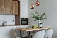 a minimalist kitchen with white and wood cabinetry, pendant lamps, a wooden table and grey chairs is very chic