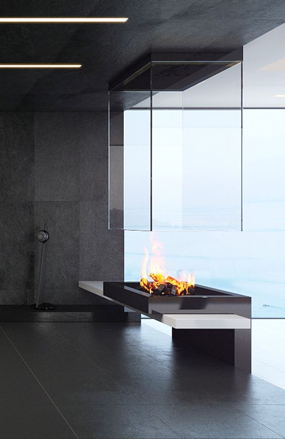 a minimalist metal, stone and glass fireplace that makes a statement and brings coziness to the space