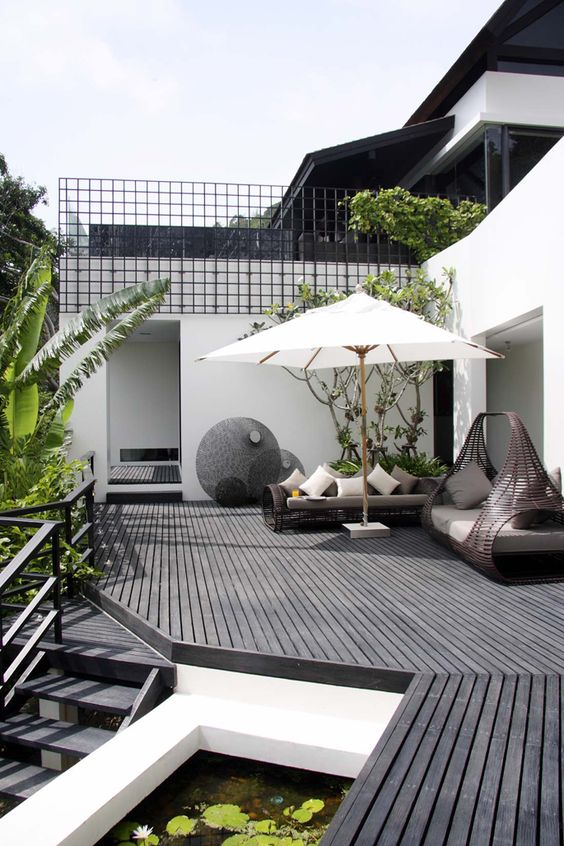 a modern black deck with dark rattan furniture, neutral textiles, a large umbrella and lots of greenery