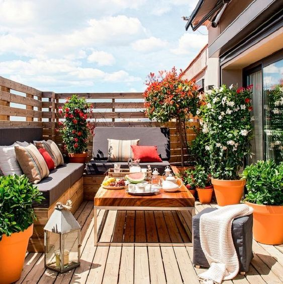 a modern deck with a corner sofa, a wooden table, a candle lantern and lots of greenery and blooms in pots