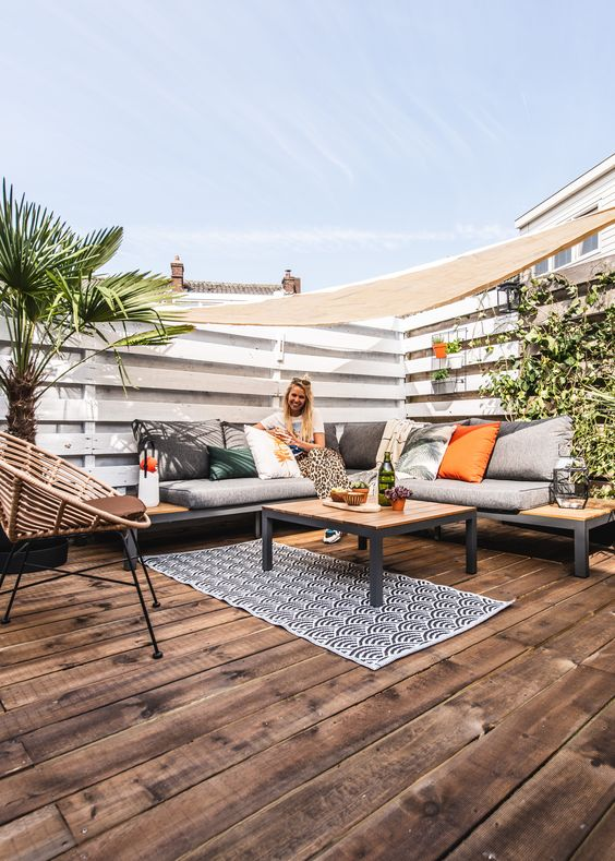 a modern deck with a corner wood and metal bench and a matching table, printed and bright pillows and greenery